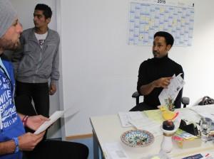 Ahmed Rokabi erläutert einem irakischen Flüchtling die Antragsunterlagen