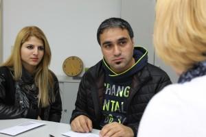 Britta Rennekamp erklärt dem jungen syrischen Paar wie es in den nächsten Tagen weitergeht