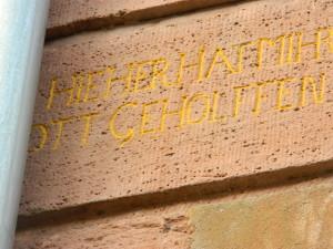 Hinter einer Regenrinne versteckt, die Inschrift, die an die Ankunft der Hugenotten in der Vorstadt erinnert. (Fotos: Corinna Willführ)