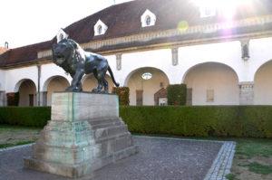 Sprudelhof: Der Bronzelöwe bewacht das Badehaus 6 im Hintergrund. (Bild: Petra Ihm-Fahle)